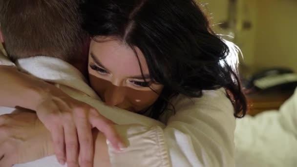 junges sexy Paar liegt nachts im Schlafzimmer in weißen Bademänteln und umarmt.