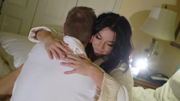 Junges sexy Paar nachts im Schlafzimmer im weißen Bademantel und umarmt.