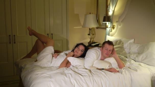 Junges sexy Paar nachts im Schlafzimmer im weißen Bademantel oder Handtuch zu legen und vor dem Sex umarmt. Romantisches Date der jungen Frau und Mann