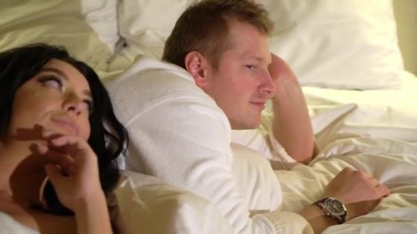 Junge sexy Paar in der Nacht liegen dim im Schlafzimmer in weißen Bademänteln oder Handtuch und Umarmung.