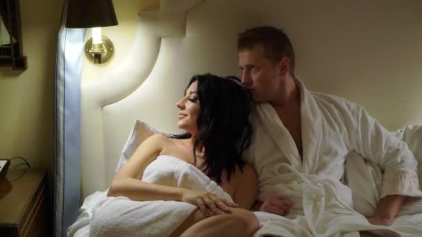 Junges sexy Paar nachts im Schlafzimmer im weißen Bademantel oder Handtuch und umarmt.
