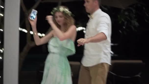 Ein junger Mann und ein Mädchen tanzen auf einer Party. Nacht Feier von Hochzeit, Geburtstag, Jubiläum oder Jubiläum. eine Veranstaltung in einer Luxusvilla in den Tropen.