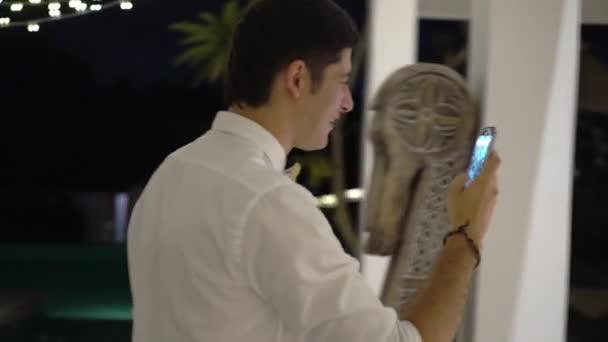 ein junger Mann macht nachts auf einer Party in einer tropischen Villa Fotos und Videos mit dem Handy