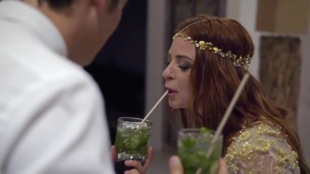 Ein junges Mädchen und ein Mann auf einer Party Cocktails trinken.
