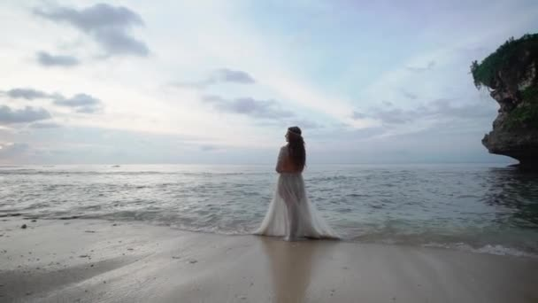 Young bride on the beach near sea at the evening or sunsetposing. Romantic near ocean.