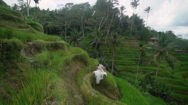 Recién Casados Sentados Y Posando En La Terraza De Arroz En Bali Manos Sosteniendo Abrazando Boda Romántica