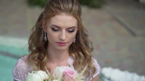 Mladá blondýna sexy žena ve spodním prádle pózuje s svatební kytice v zahradě poblíž fountain