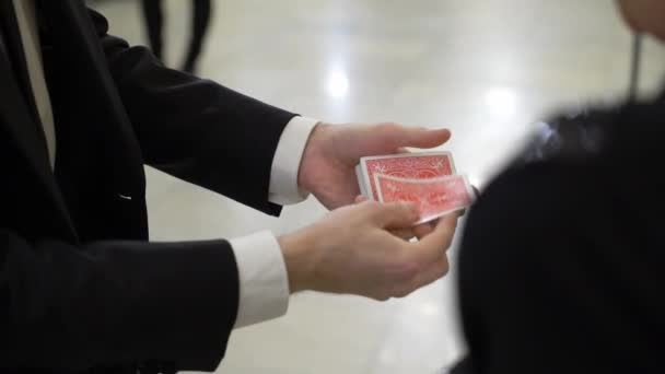 Magier hält Spielkarten, zeigt Fokus, jongliert