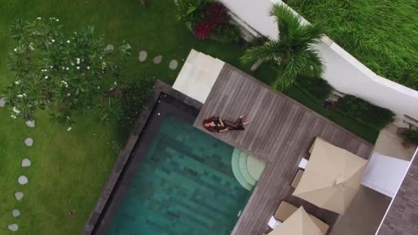 Mladá sexy žena v černém prádle pokládání bazénu v luxusní vile