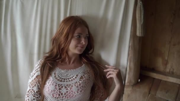 ein junges Mädchen in einem transparenten hellen Kleid, das in einer Hängematte liegt. rothaarige schöne Mädchen im Urlaub.