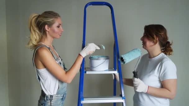zwei Arbeiterinnen mit Walzen, um die Wände in der Wohnung oder im Haus zu streichen. Bau, Reparatur und Renovierung.