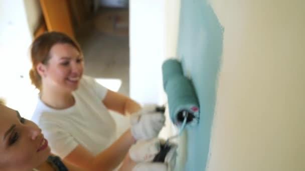 Dva dělníci žena pomocí válec k malování zdí v bytě nebo domě. Výstavba, opravy a renovace.