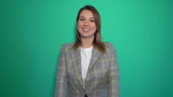 Young cheerful caucasian woman showing thumbs up over green background