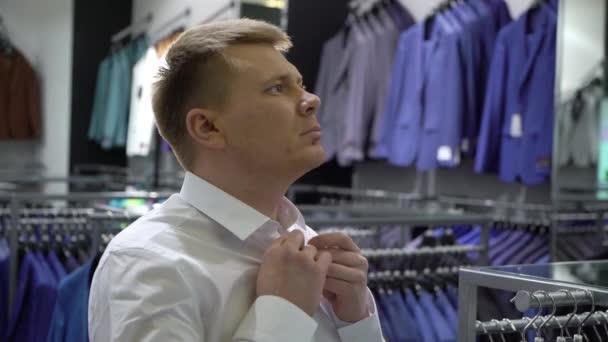 Vásárlás és divat koncepció-fiatal férfi kiválasztása és próbál zakó a bevásárlóközpontban, vagy ruházati bolt