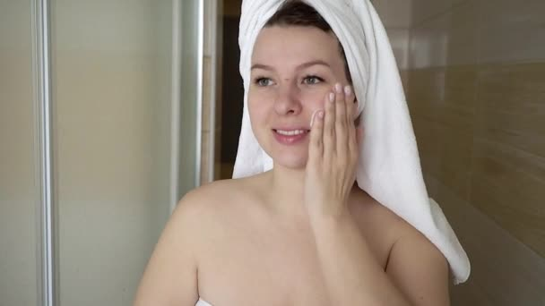 Woman cleaning washing her face with foam in bathroom