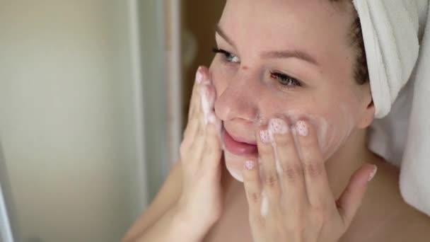 Nő takarítás mosás arcát a hab a fürdőszobában