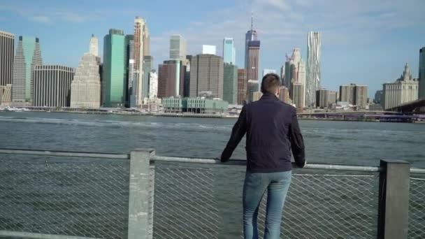 Mladý muž se dívá na mrakodrapy