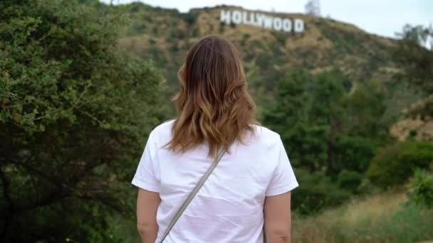 Young woman walking near Hollywood sign