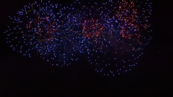 Gyönyörű tűzijáték, amely megvilágítja és színezi a sötét éjszakai égboltot. videó