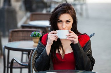 Outdoors fashion portrait of young beautiful girl drinking coffee.Close up portrait of a smiling young girl holding take away coffee cup outdoors.Young stylish woman drinking coffee in a city street