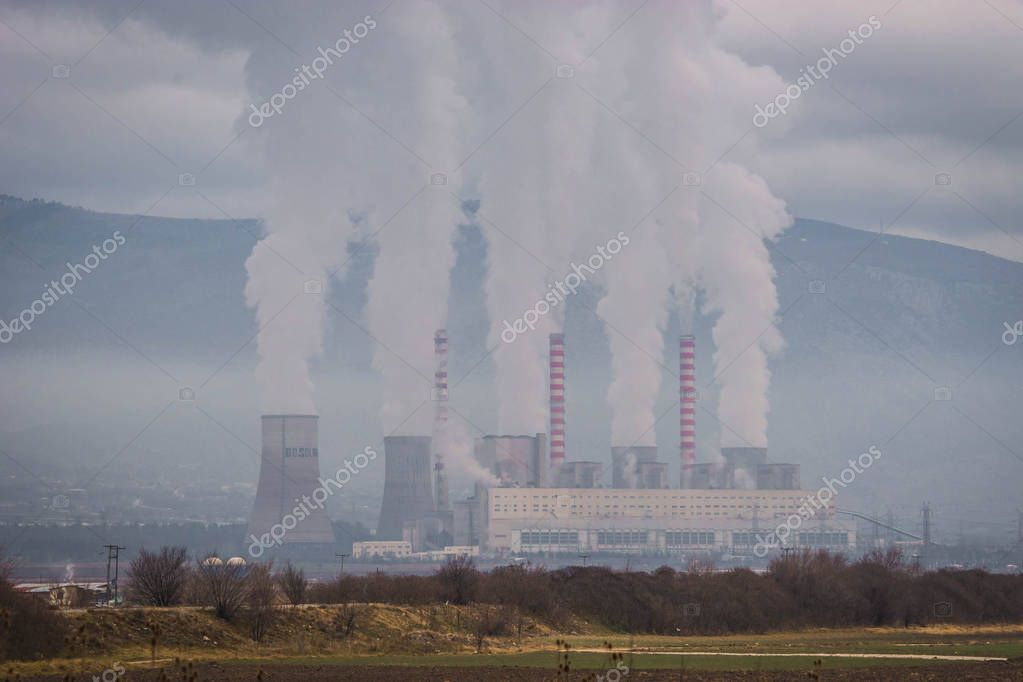 Smoking chimneys of plant in field near road in northern Greece
