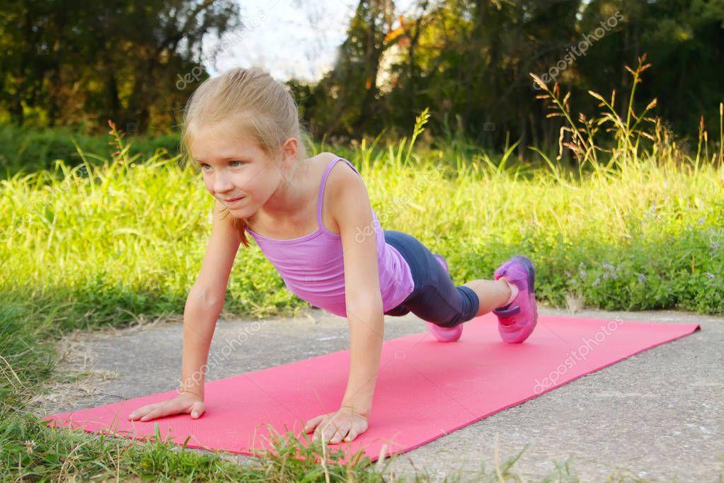 Little blond girl doing fitness exercises plank in the park
