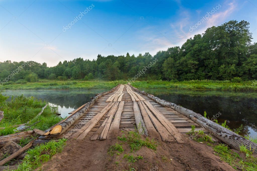 Temporary wooden bridge across river for heavy lorries, trucks, cars and vehicles  for carriage wood during deforestation