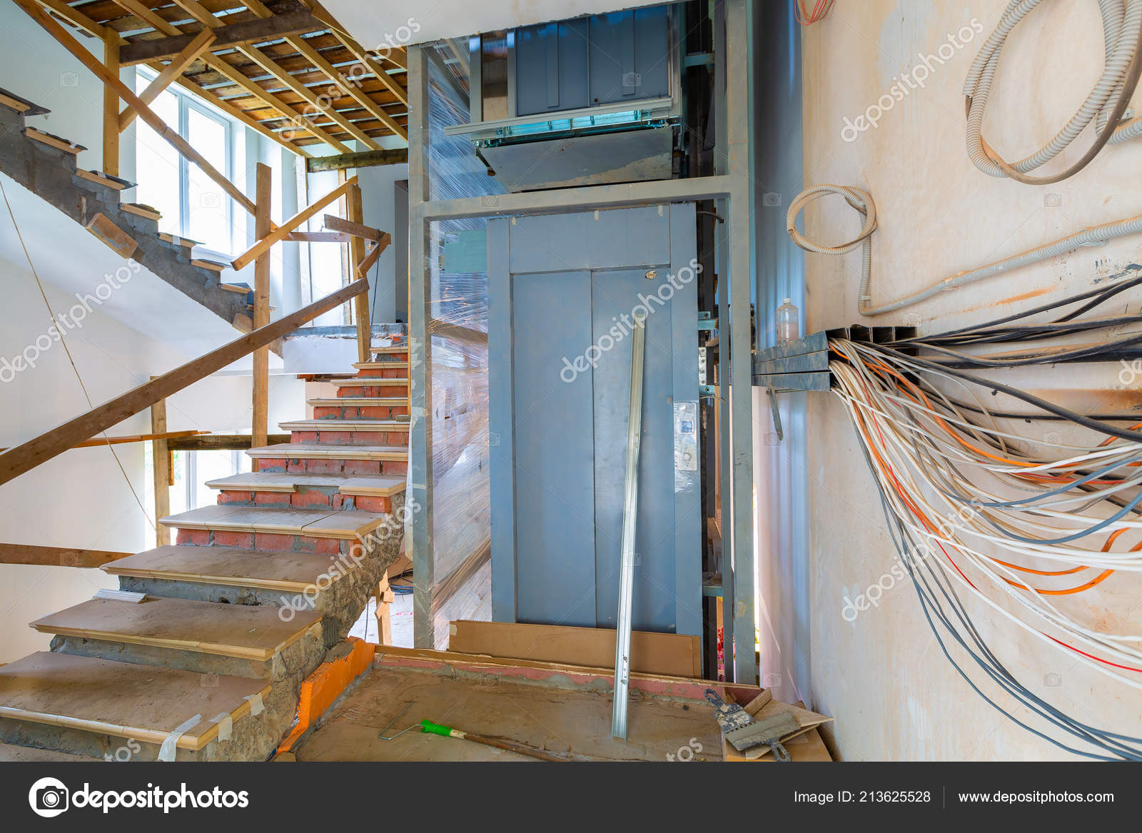 Wall with wires, stairs with temporary wooden railing and