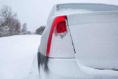 View focused on the back red tail lights of car  and car trunk  or car boot   on winter road covered with snow. Vehicle on snowy road after snowfall.