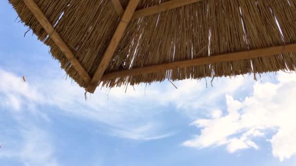 4k Video Nahaufnahme von Strand Strohschirmecke mit blauem Himmel und Wolken am Meer und kleinen Windböen