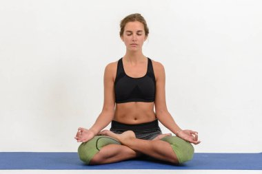 Beautiful young woman doing yoga on white background