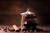 Chocolate pieces with coffee beans and cinnamon on wooden table