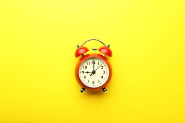 Red alarm clock on yellow background