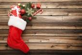 Fotografie Červená Punčocha s větve jedle a vánoční ozdoby na dřevěný stůl