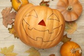 Photo Halloween pumpkin with dry leaves on wooden table