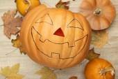 Halloween dýně s suché listí na dřevěný stůl