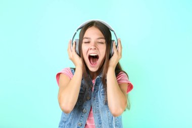 Young girl with headphones on mint background
