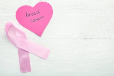 Pink ribbon with inscription Breast Cancer on white wooden table