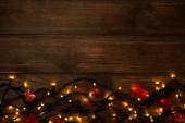 Fotografia Ghirlanda di luci con decorazioni di Natale sulla tavola di legno marrone