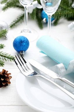 Kitchen cutlery with plate and christmas decorations on wooden table