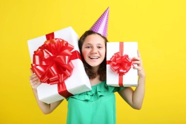Beautiful young girl  in birthday cap holding gift boxes on yellow background stock vector
