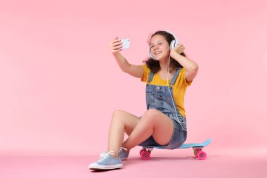 Young girl making selfie and sitting on skateboard on pink background