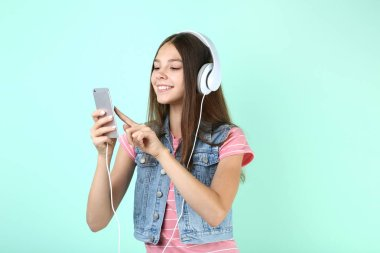 Young girl holding smartphone and listening to music on headphones on mint background