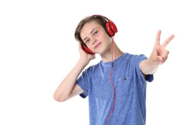 Cute teenager boy listening to music on headphones and  showing peace symbol on white background