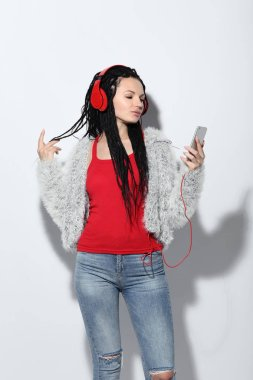 Young woman in fashion clothes holding smartphone and listening to music on headphones on white background