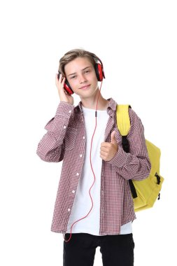 Young boy with yellow backpack listening to music on headphones isolated on white background