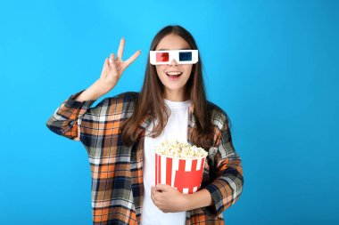 Young girl in 3d glasses holding bucket with popcorn and showing peace symbol on blue background stock vector