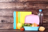 School lunch box with sandwich and colorful notebooks on wooden table