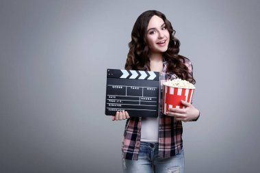 Young beautiful woman holding bucket with popcorn and clapper board on grey background stock vector