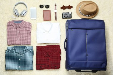 Blue suitcase with clothes, headphones, smartphone and passport